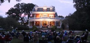 group of people sitting on lawn chairs in front of ellwood house museum listening to music