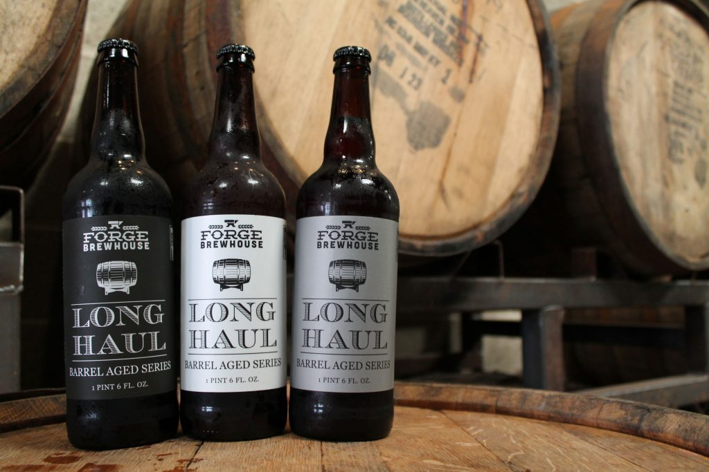 forge brewhouse long haul beer with barrels in the background