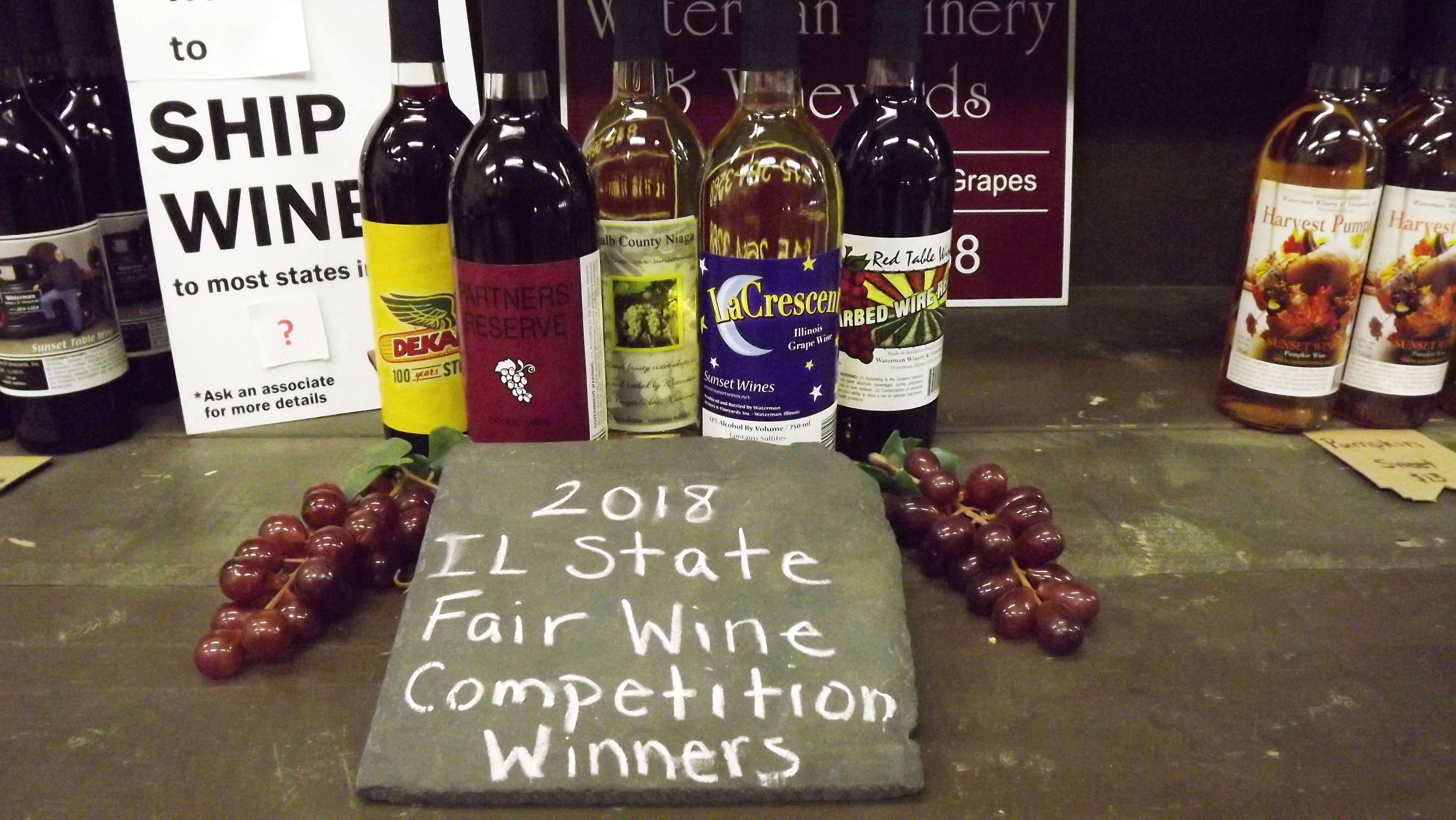 """bottles of wine with a slate reading """"2018 illinois state fair wine competition winners"""""""